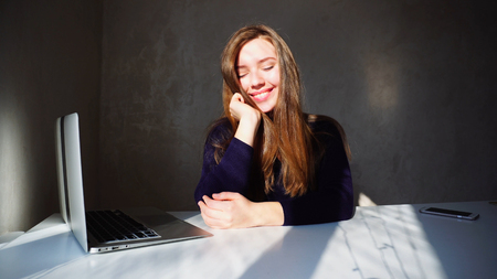 Dimpless Student sitting at table smiling and working with laptop. Young European caucasian girl has long blond hair and dimples. Concept of success, new advanced technology, student work at home or office.