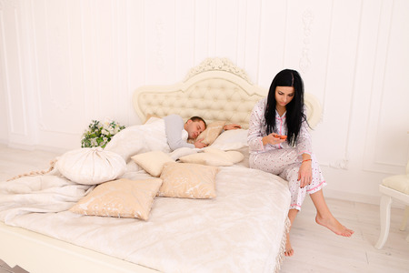 celos: Woman reading conversation while man sleeps. Female does not trust her boyfriend jealous. Couple European appearance. concept of family life, young couple living together, mistrust, jealousy and recriminations.