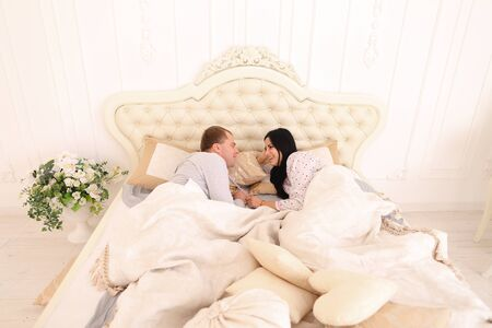insult: Mom, Dad lay on bed and looking at each other, talk and insult. Luxury furniture and beautiful interior in bright colors. Mom with black long hair, Dad European appearance smiling. Concept of happy life family values, success. Family main thing in life. Stock Photo