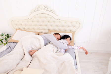 Mom, Dad lay on bed. Girl asleep, guy hugging wife about problems at background of Luxurious furniture  beautiful interior in bright colors. Mom with black long hair, Dad European appearance. Concept of happy life family values or financial problems. Man