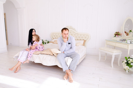 After argument Female hugging daughter man sad looking out window. Young couple find out relationship and family problems. Woman with long black hair, brown man and blonde daughter european appearance on background white interior. Concept of family life f Stock Photo