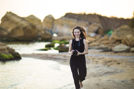 Young woman photographer holding camera and looking into frame. Girl dressed in black jumpsuit, European appearance. Concept of feminine beauty,  work photographer tourist with camera on vacation or trip. Stock Photo