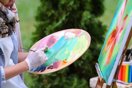 Photo of female hand artist who mixes oil or acrylic colored bright colors on wooden panel, which would start to draw and located in green park in open air. Concept of set of objects to paint, oil or acrylic paints, advertising art school.