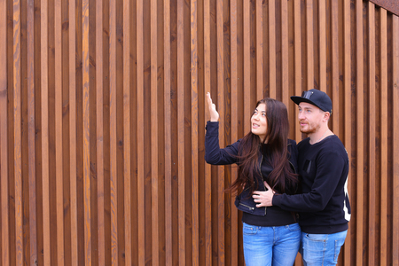 Bride and groom embracing each other, looking to sky and come up forms of clouds, dreaming about future together, enjoy each others arms, will not hurry and rest, stand near wooden walls of restaurant outdoors. Man dressed in black sweater, blue jeans, s