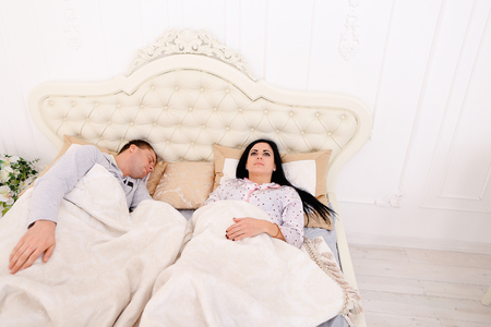 Mom, Dad lay on bed. Girl asleep, thinking about problems at background of Luxurious furniture  beautiful interior in bright colors. Mom with black long hair, Dad European appearance. Concept of happy life family values or financial problems. Female not k