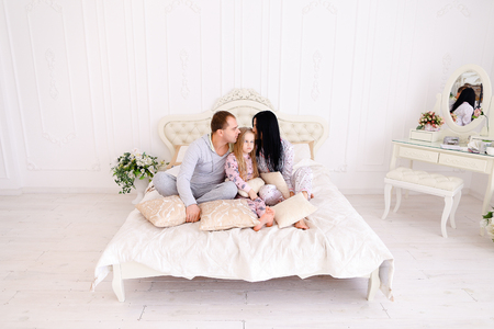 pyjama: Child, mom and dad sit on bed, smiling and looking at camera. Young happy couple together. Woman with long black hair, brown man and daughter blonde European appearance against white interior. Concept of family life, happiness and joy.