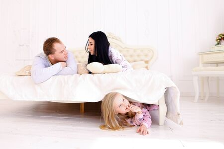 nightwear: Child hides under bed where parents talk and smile. Young happy family together. Woman with long black hair, brown man and daughter blonde European appearance against white interior. Concept of family life, happiness and joy, good morning. Stock Photo