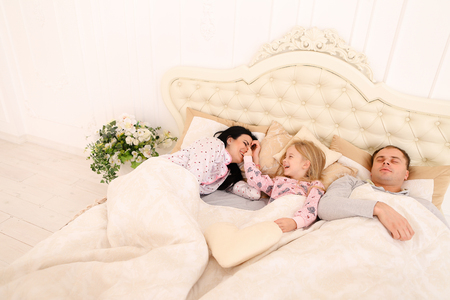 Girl having fun, teases parents nose, she wakes them and wants young couple woke up. Mom with black long hair, Dad European appearance, a daughter with long white hair smiling. Concept of happy family attitudes, values, happy life, good morning, childhood Stock Photo