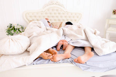 Husband, wife and daughter sleep in bed. Taking Close-up family feet to embrace. Mom, Dad European appearance. The concept of a happy family life, success, entertainment, advertising, Hotels or bed linen or furniture. Stock Photo