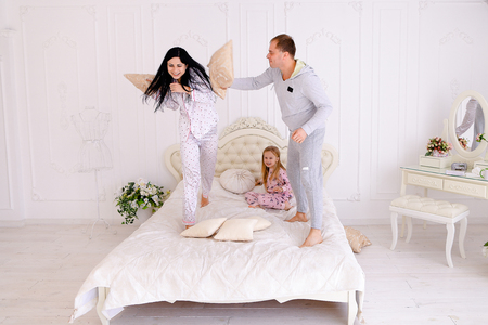 Mother, father, daughter jumping on bed and looking at camera. Luxury furniture and beautiful interior in bright colors. Mom with black long hair, Dad European appearance, daughter with long white hair smiling. Concept of happy life, family values, succes Stock Photo