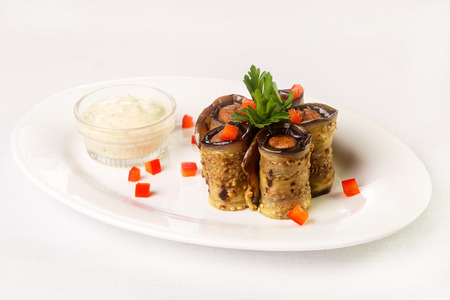 Main course, rolls of grilled aubergines with meat and vegetable filling inside, next to sauce bowl made of glass with white cream sauce on white oval plate on light background. Concept of appetizing and beautiful food, restaurant serving of snacks and ma Imagens