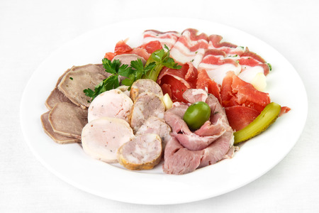 Beautifully laid out, thinly sliced meat slices on round and white plate on light background. In cart of cakes cut tongue and bacon, sausages and ham and decorated with greens with salty crispy cucumbers. Concept of meat products and bacon slicing, delica