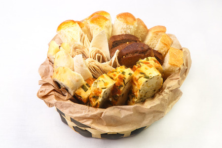 Assorted baked goods, white and black bread with herbs and herbs, and pita bread in round deep small wicker basket covered with parchment on white background. Concept of tasty and useful pastries, baked goods from wheat and rational nutrition, pleasure an