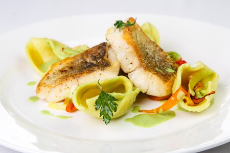 Tasty and fried on frying pan Hake fillet with golden crust in aromatic spices and in light green sauce with dough ornaments on round and white plate on light background. Concept useful tasty and beautiful food, appetite with pleasure and taste, restauran