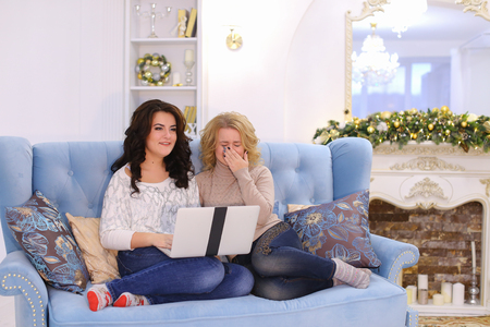continue: Attractive young women and girlfriends look at laptop thriller or horror film, women frightened and periodically close their eyes with their hands, afraid but continue to watch movie together. Girls of European appearance sit on blue and beautiful sofa wi Stock Photo