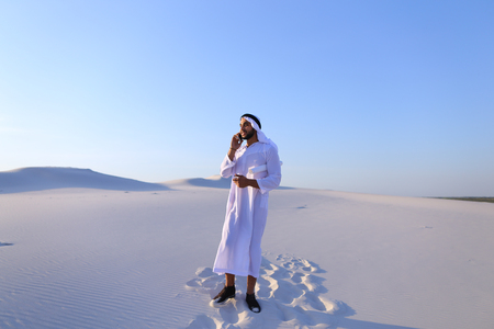 Successful Arab young male architect keeps in hands and looks at project drawing, finishes work and answers incoming call of customer, talks about progress of construction and news, standing in middle of big desert outdoors on hot summer day. Swarthy Musl