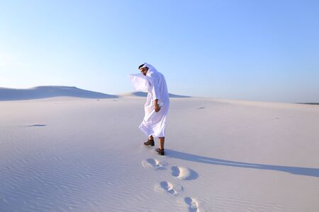 spreads: Handsome young Emirate strolls and looks around wide desert with white sand. Muslim smiles with all teeth and spreads hands to sides, amazed at greatness of nature, straightens clothes in wind and whirls around. Swarthy, handsome Muslim with short dark ha Stock Photo