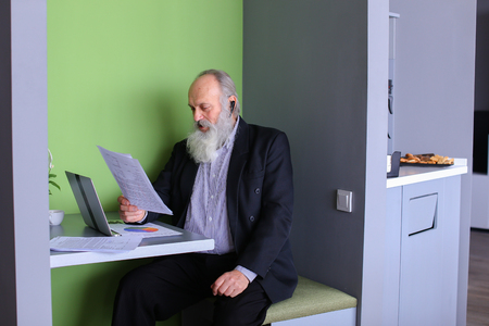 interbank: Senior citizen analyzes financial situation of company and conducts operations on interbank loans market using computer and negotiating wireless headset while sitting in stylish office cafe on sunny day. Elderly man with long gray beard of European appear