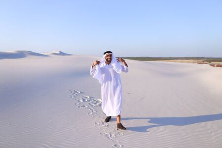 Stately young sheikh walks on foot along bottomless desert leaving traces on sand, enjoying warmth of day. Attractive Muslim smiles widely and spreads hands to sides, straightens clothes in wind and whirls around, delighted by breadth of desert. Swarthy,  Stock Photo