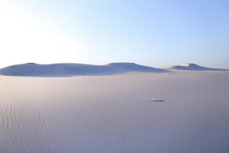 Landscape of bottomless and deserted white desert with barkhans and sand dunes of pure white sand under open blue clear sky on hot summer day. Concept of wildlife and environment, sandy desert, hot country and travel.