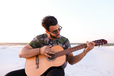 sho: Ambitious budding musician, Muslim guy performs lyrical melody on musical instrument and guitar, and raises skill of professionalism, sitting on sandy hill in middle of wide sandy desert on warm summer evening at sunset. Swarthy man with dark hair and sho