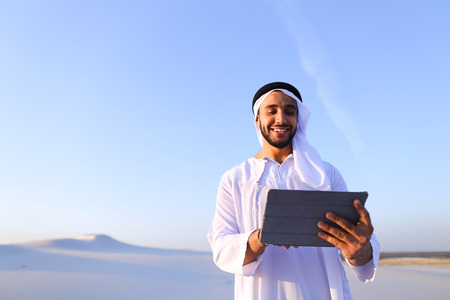 Handsome Muslim businessman with tablet solves important work issues and problems, smiles and moves finger along touch screen of gadget, standing on white clean sand in desert outdoors on warm summer evening. Swarthy Muslim with short dark hair dressed in