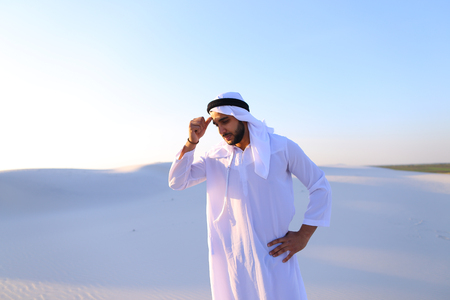 Portrait of tired Arab man, who holds head and feels migraine, tries to calm pain and massages whiskey, standing in middle of bottomless desert with snow-white sand on sunny summer day. Swarthy Muslim with short dark hair dressed in kandura, long, spaciou Stock Photo