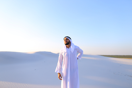 Frustrated fellow emirate suffers from back pain and holds on to waist, feels heaviness and tries to stretch back to improve condition, standing in middle of bottomless desert with white sand on sunny summer day. Swarthy Muslim with short dark hair dresse