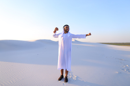 Handsome young Emirate strolls and stretches, spreads hands to sides and rests from city bustle, examines surroundings of wide desert with white sand. Swarthy Muslim with short dark hair dressed in kandura, long, spacious dress made of white unpainted cot Stock Photo