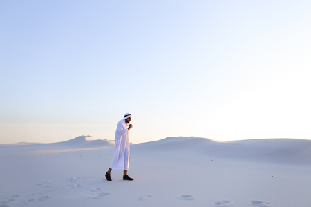 breadth: Handsome young Muslim driving along bottomless desert and looking toward sunset, admiring beauty of nature on warm clear night. attractive Muslim smiles widely and spreads hands to sides, straightens clothes in wind and whirls around, delighted by breadth