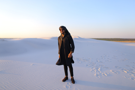 he: Handsome Emirate man walks white sand of desert, smiles broad smile and looks around neighborhood. Guy spreads hands to sides and shows gesture of successful man, he screams at top of voice with joy and emotion, standing in midst of bottomless desert with Stock Photo