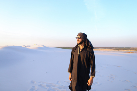 Handsome Emirate man walks white sand of desert, smiles broad smile and looks around neighborhood. Guy spreads hands to sides and shows gesture of successful man, he screams at top of voice with joy and emotion, standing in midst of bottomless desert with Stock Photo