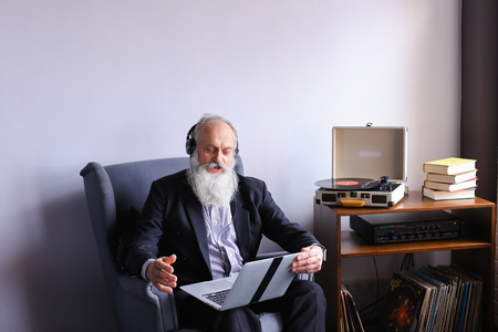 websurfing: Retired person male dancing sitting in headphones and with computer on his lap sings songs aloud in comfortable soft gray glue next to curbstone with books, music plates and bedroom in bright room opposite window. Elderly man with long gray beard of Europ Stock Photo