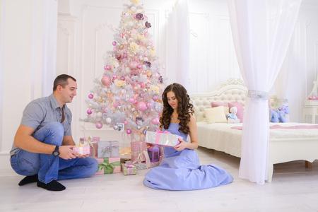 Jonge ouders gelukkige man en vrouw nemen uit onder kerstboom met geschenkdozen en geven elkaar uit het hoofd. Familie op drempel van Nieuwjaarsdagen glimlachen en elkaar kussen. Leuk wijfje met lang donker golvend haar gekleed in lange blauwe kleding, Ha