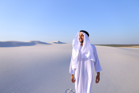 Cheerful Muslim guy walks along white sand of wide desert on warm summer evening. Arab young man in national clothes dances on spot and laughs giggly, adjusting hands with harness in wind. Swarthy, handsome Muslim with short dark hair dressed in kandura,  Stock Photo