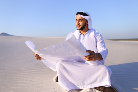 Educated Muslim guy entrepreneur and designer reads project of future construction, comes up with interesting designs and puts hand to chin with smile on face, sitting in middle of wide desert with white clean sand on clear warm day on background of blue