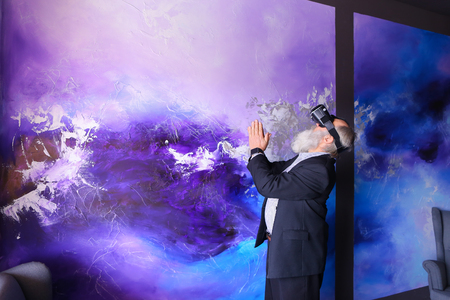 Elderly man in VR glasses outside imagination felt virtual reality and enjoys seen and new technologies. Old man with long gray beard of European appearance dressed in black classic suit and white shirt in blue stripes and stands on background of bright c