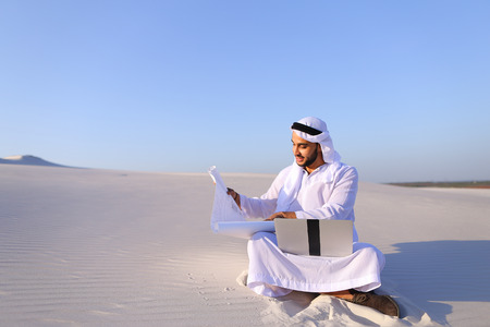 Stately Arab male entrepreneur holds in hands and examines project on paper, compares with future site for construction and transfers data to laptop, sitting on white sand in bottomless wide desert in afternoon against blue sky. Swarthy Muslim with short  Stock Photo