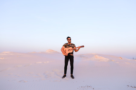Young Muslim man stands at full length and plays melody on stringed musical instrument, takes chords, smiles and sings to himself, inspired by surrounding landscape, standing in midst of wide sandy desert on warm summer evening at sunset. Swarthy man with