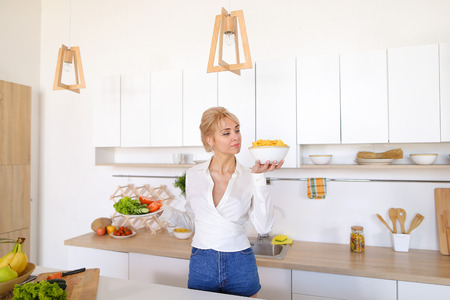 kitchen cabinets: Attractive young woman presents dinner in plates, holds flat plate with tomatoes, cucumbers and lettuce leaves and deep plate with potato chips in palms, smiling with beautiful smile, standing in stylish light kitchen against backdrop of cabinets and vari