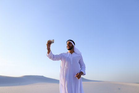 background skype: Happy, handsome guy, emirate and tourist, conducts dialogue through Internet with help of device, waves hand and smiles at camera of smartphone, shows beautiful views and sights of large sandy desert outdoors on summer day. Swarthy Muslim with short dark  Stock Photo