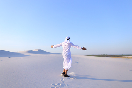 broadly: Successful Muslim tourist guy smiles broadly and spreads hands to sides and whirls around, laughs and smiles in desert on clear warm day. Swarthy, handsome Muslim with short dark hair dressed in kandura, long, spacious dress made of white unpainted cotton Stock Photo