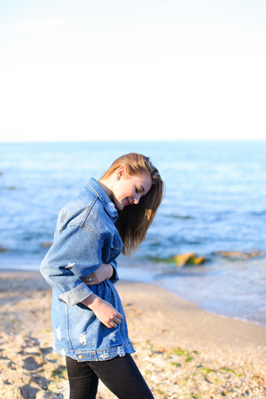 Beautiful young woman with necessary smile looks afar at sea waves, closes eyes with pleasure and listens to sound of surf, poses and warms from cool wind from sea on clear cool evening. Woman of European appearance with blond mid-length hair dressed in b