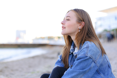 Cheerful young woman with smile on lips closes eyes from happiness and looks into camera, giggles and laughs and enjoys view of sea waves and boundless sky. young European-looking woman with fair-haired middle-length hair dressed in blue denim jacket and