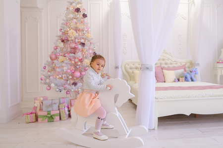 Sweet girl baby swinging on rocking horse toy, smiling and looking at camera. Little blonde girl with bow on  head dressed in peach dress and white jacket trim, pink tights with pattern and white shoes with white background on spacious bedroom light Chris
