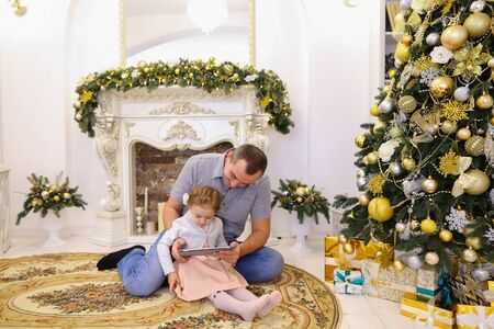Cute little girl child holding gadget and plays game running his finger along touchscreen via his father, handsome man who told girl how to use tablet and sitting on background of fireplace with candles decorated Christmas tree and yellow balls and mirror