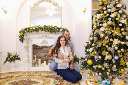 tenderly: Lovers man and woman, young family tenderly embrace each other and kiss, pose for photograph sitting on carpet near beautiful decorated Christmas tree and fireplace with candles in bright and comfortable room. Cute female with long dark wavy hair dressed  Stock Photo