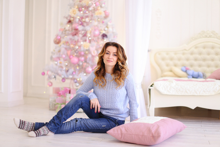 Elegant female smiling and posing near  pillow for photo in memory in festive bright bedroom sitting on floor on background of Christmas tree and big beautiful bed in cold winter day. European-looking girl with long curly hair dressed in blue sweater and