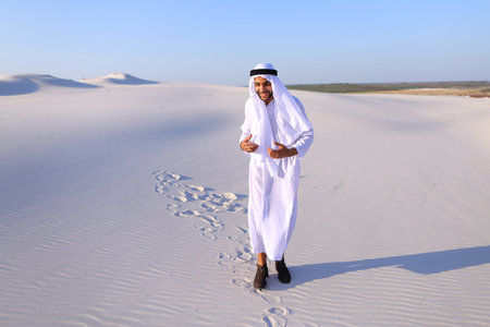 widely: Stately young sheikh walks on foot along bottomless desert leaving traces on sand, enjoying warmth of day. Attractive Muslim smiles widely and spreads hands to sides, straightens clothes in wind and whirls around, delighted by breadth of desert. Swarthy,  Stock Photo