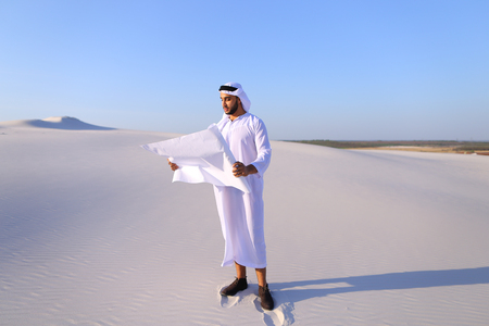 Beautiful Emirate Sheikh businessman studying project of future construction of complex, standing in middle of bottomless desert with white clean sand on clear warm day against blue sky. Swarthy Muslim with short dark hair dressed in kandura, long, spacio Stock Photo